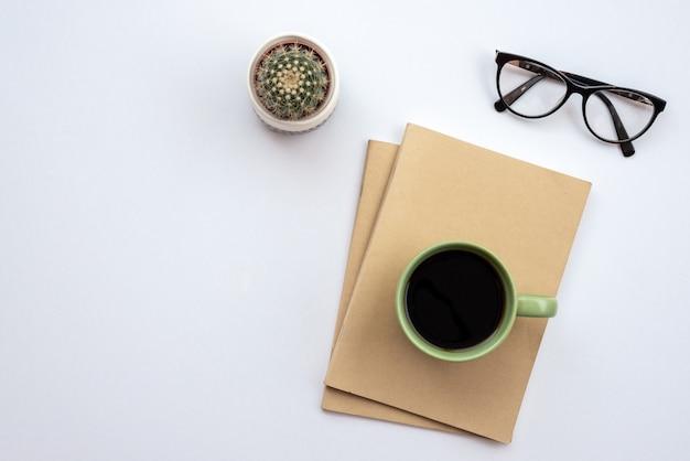 Weißer schreibtisch im büro mit gläsern, tasse kaffee und kaktus. - draufsicht