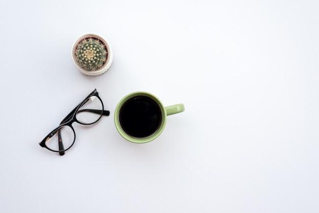 Weißer schreibtisch im büro mit gläsern, tasse kaffee und kaktus