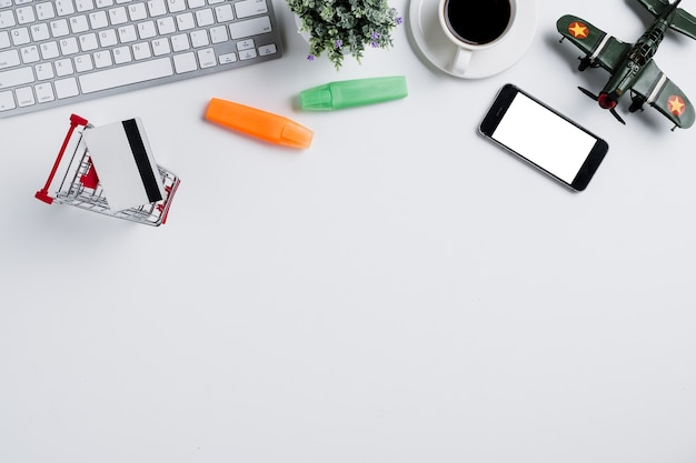 Weißer schreibtisch mit computertastatur, notebook und zubehör