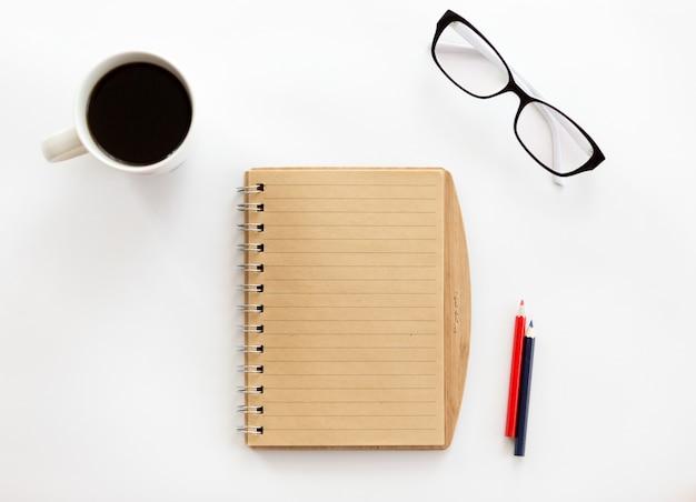Weißer schreibtisch mit einem notizbuch und bleistiften, gläser