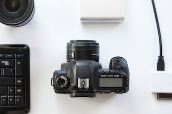 Weißer Schreibtisch mit einer professionellen Kamera und Zubehör auf sie