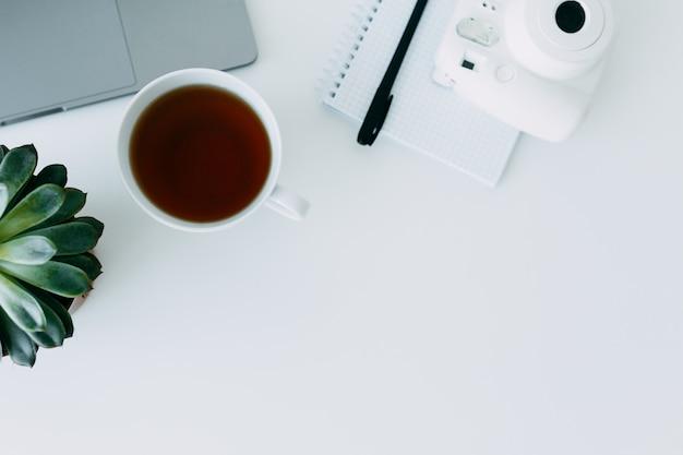 Weißer schreibtisch mit laptop, büroanlage und notizbuch mit stift, minikamera und tasse tee. draufsicht mit kopienraum, flach legen
