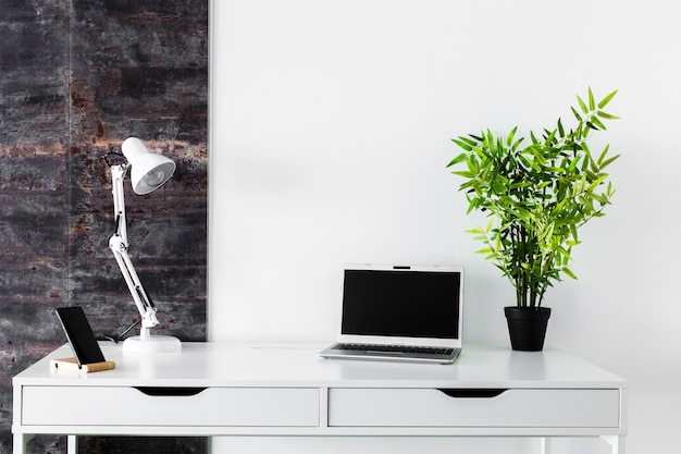 Weißer schreibtisch mit laptop und lampe