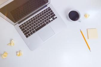 Weißer Schreibtisch mit Notizen, Kaffee und Laptop