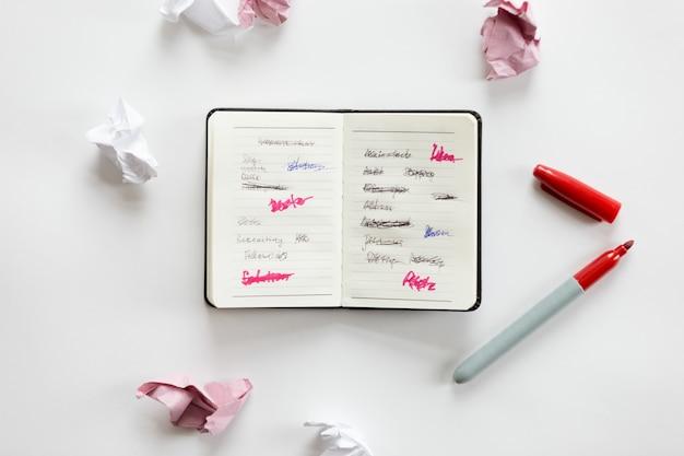 Weißer schreibtisch mit offenem notizbuch und zerknittertem papier