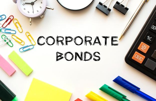 Weißer schreibtisch tisch mit taschenrechner, lupe, farbigen stiften und anderem briefpapier. text auf den corporate bonds.