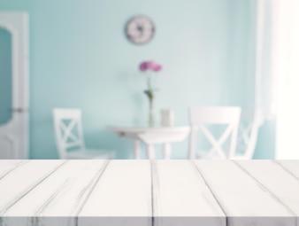 Weißer Schreibtisch vor essbarem Tisch der Unschärfe gegen die Wand