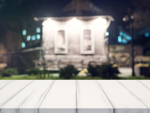 Weißer schreibtisch vor unschärfehaus nachts