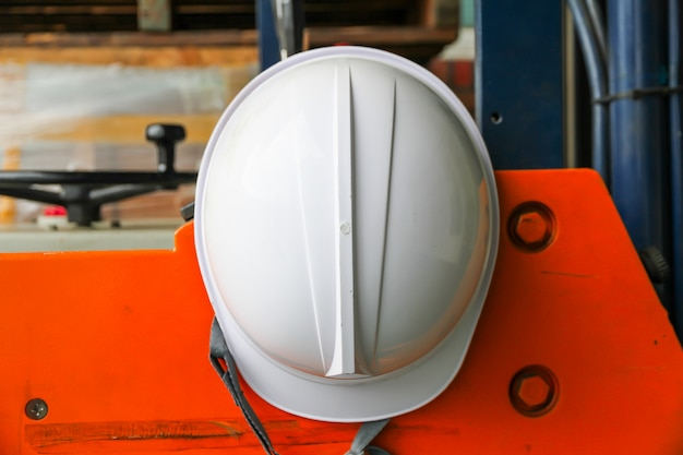 Weißer schutzhelm, der am orange gabelstapler hängt