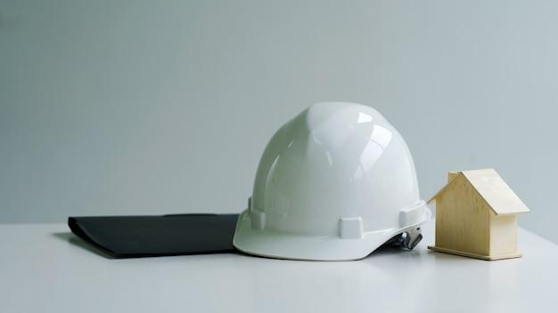 Weißer schutzhelm des arbeiterhausingenieurarbeiters auf tisch gelegt.