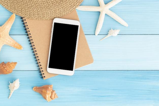 Weißer smartphone auf braunem notizbuch auf blauem hölzernem
