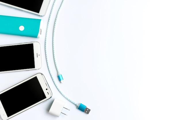 Weißer smartphone mit batterie bank und usb-ladekabel in der draufsicht
