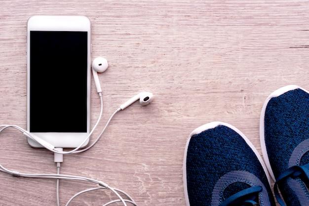 Weißer smartphone mit den kopfhörern angeschlossen, nahe bei sportschuhen. gesundes lebensstilkonzept, eignung.