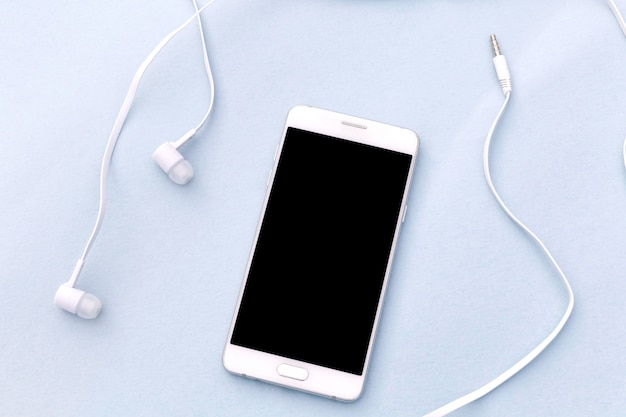 Weißer smartphone und weiße kopfhörer auf blauem hintergrund.