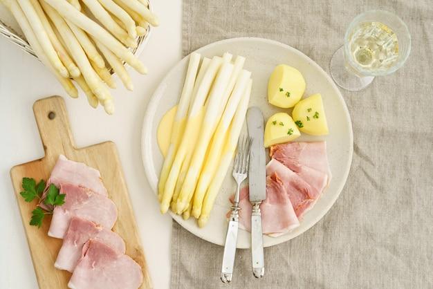 Weißer spargel mit kartoffeln und gekochtem schinken