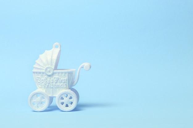 Weißer spielzeugkinderwagen auf blauem hintergrund. kopierraum.