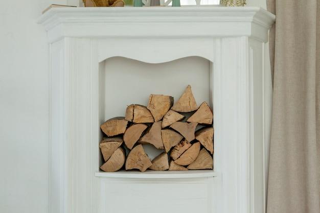 Weißer steinkamin mit brennholz ohne feuer.