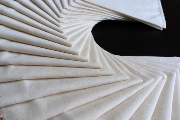 Weißer stoff gefaltet oder gestapelt. stoff textur hintergrund. konzeptworkshop