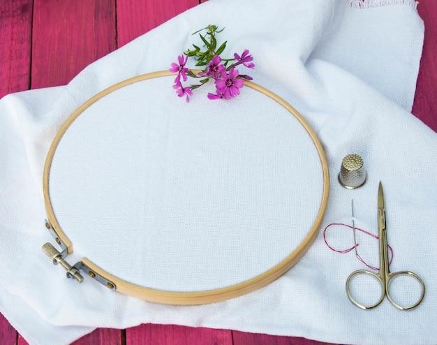Weißer stoff zum besticken in rundem stickrahmen aus holz