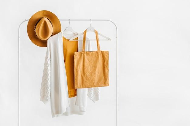 Weißer strickpullover auf kleiderbügel mit brauner mütze und öko-tasche auf weißem hintergrund. elegantes mode-outfit. frühlingsgarderobe. minimales konzept.
