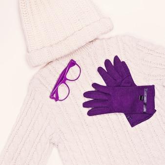 Weißer strickpullover und mütze in kombination mit lila handschuhen. wintermode-stil