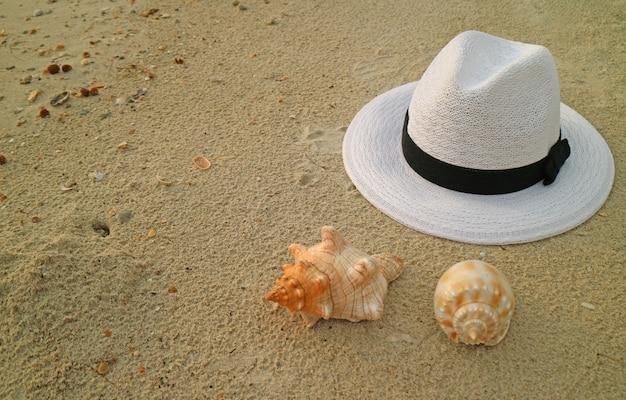 Weißer strohhut am sandstrand