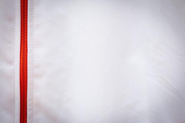Weißer strukturierter nylongewebemusterhintergrund mit orangefarbenem reißverschluss für design