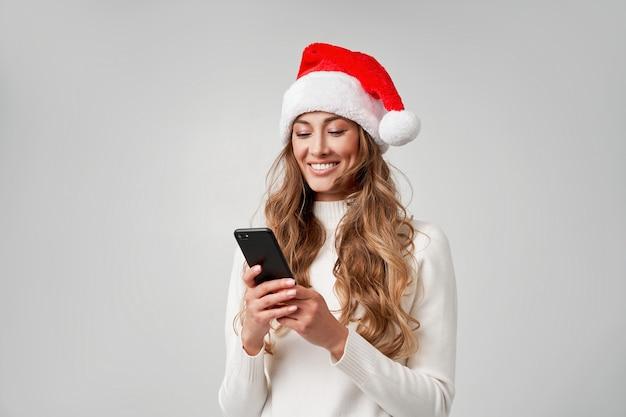 Weißer studiohintergrund der frauweihnachts-weihnachtsmannmütze mit smartphone in der hand