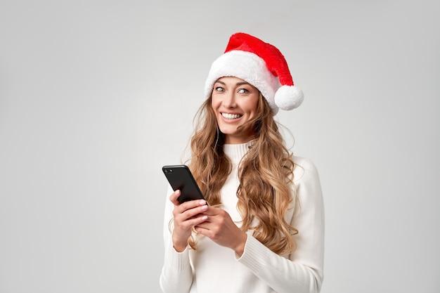Weißer studiohintergrund des weihnachtsmann-weihnachtsmanns der frau mit smartphone in der hand
