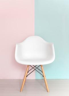 Weißer stuhl auf pastellfarbenem hintergrund