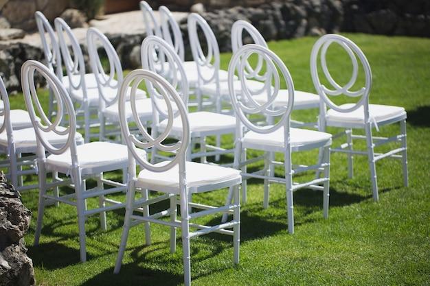 Weißer stuhl, der für hochzeitszeremonie verziert