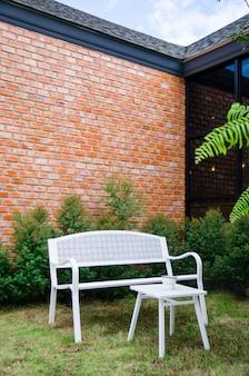 Weißer stuhl im garten mit backsteinmauerhintergrund