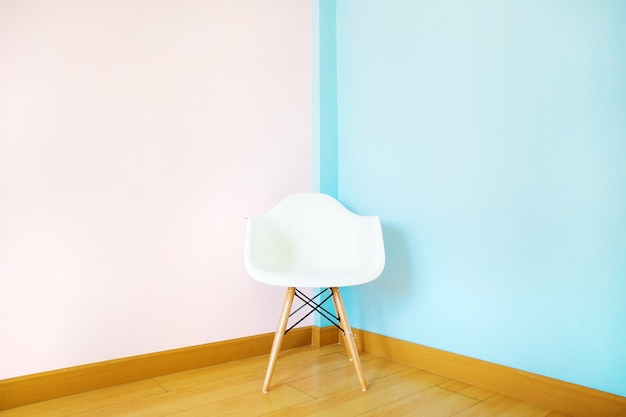 Weißer stuhl im wohnzimmer auf pastellwand