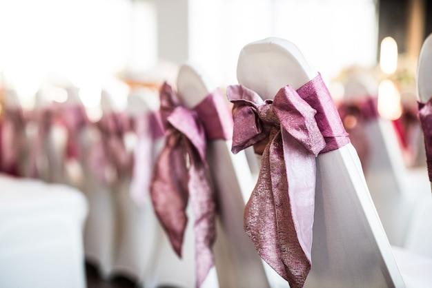 Weißer stuhl mit rosa schleife für die zeremonie