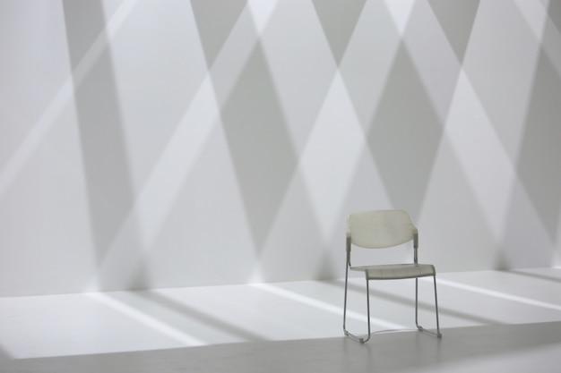 Weißer stuhl vor diamantformschattenwand