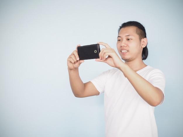 Weißer t-shirt gebrauch-handy der asiatischen jungen hippie-mannabnutzung, zum von fotografie zu machen