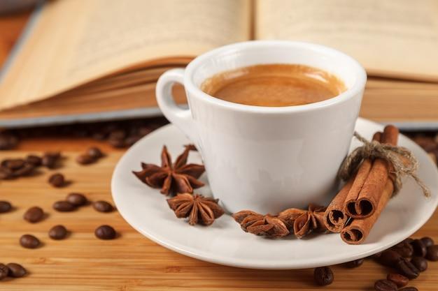Weißer tasse kaffee-espresso, umgeben von gerösteten kaffeebohnen