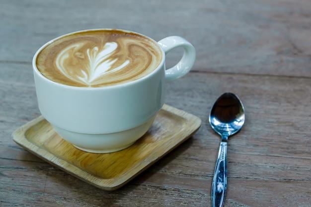 Weißer tasse kaffee latte auf dem hölzernen schreibtisch, zeit bereits genossen kaffee, weichzeichnung auf capuccino-kaffee
