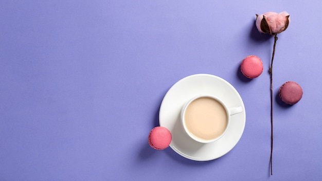 Weißer tasse kaffee mit milch und geschmackvollen macarons, baumwollblume auf einem empfindlichen lila hintergrund. draufsicht, kopie, raum. frühlingsgrußkarte, tapete