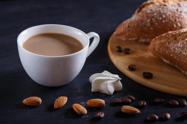 Weißer tasse kaffee mit sahne und brötchen auf einem schwarzen hintergrund