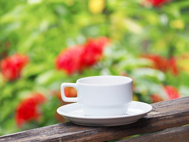 Weißer tasse kaffee über grünem abstraktem unschärfemit blumenhintergrund.