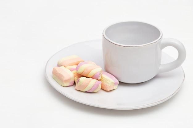 Weißer tasse kaffee und bonbons auf tabelle. dessert zum frühstück. copyspace.