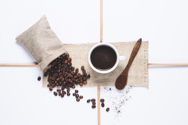 Weißer tasse kaffee und kaffeebohnen liefen de-beutel über