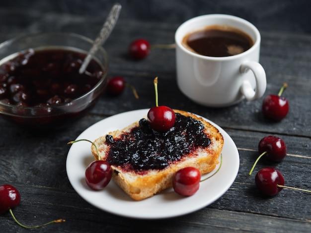 Weißer tasse kaffee und toast mit kirschmarmelade auf weißer platte auf schwarzer tabelle
