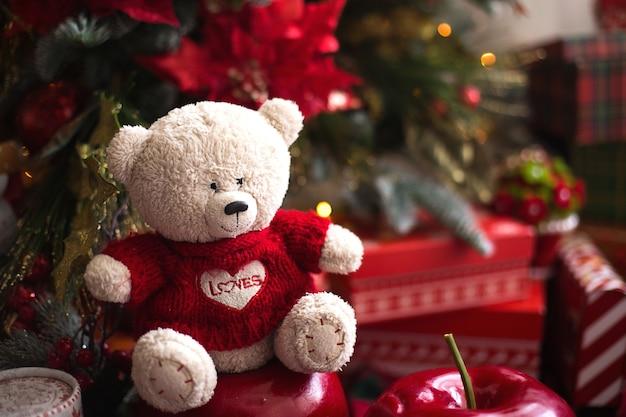 Weißer teddybär im roten strickpullover mit herz auf der brust und den worten liebe nahe weihnachtsbaum
