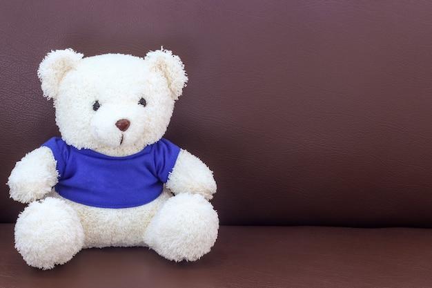Weißer teddybär mit blauem hemd auf dem sofa