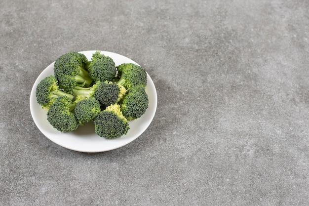 Weißer teller des gesunden frischen brokkolis auf steintisch.