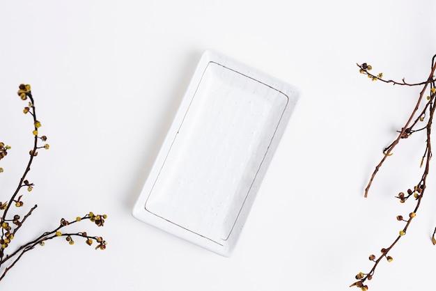 Weißer teller im flat-lay-stil mit trockenblumen