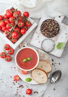Weißer teller mit cremiger tomatensuppe mit löffel auf hellem tisch mit schachtel mit rohen tomaten und brot. draufsicht