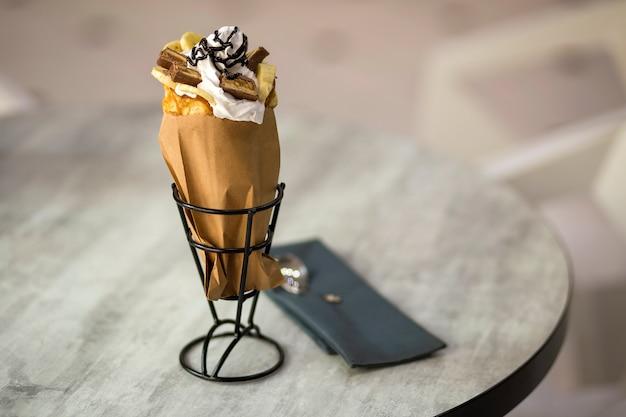 Weißer teller mit eisdessert in der waffelschale mit schokoladenplätzchen und kreativer dekoration, die auf unscharfem buntem innenhintergrund übersteigen.
